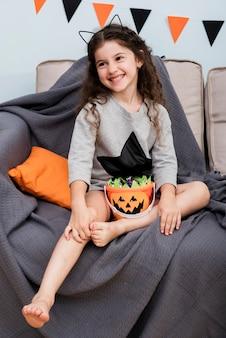 Вид спереди маленькая девочка, сидя на диване на хэллоуин