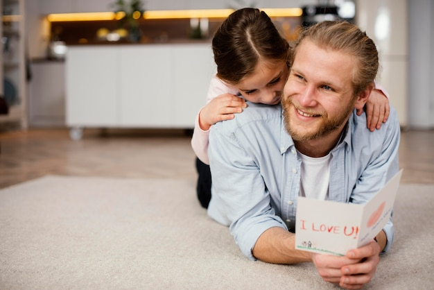 Front view of little girl spending time with father with copy space