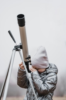 Front view little girl using a telescope