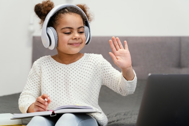 Front view of little girl waving and using laptop for online school