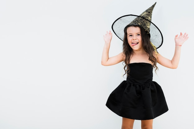 Front view little girl in witch costume with copy space
