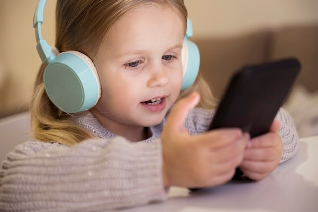 Front view of little girl with headphones and phone