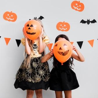 Вид спереди маленьких девочек в костюме ведьмы на хэллоуин