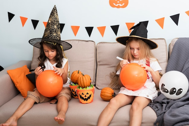 Front view little girls sitting on couch on halloween