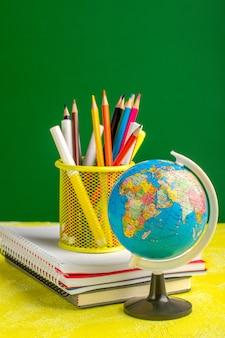 Piccolo globo di vista frontale con i quaderni e le matite sulla superficie gialla