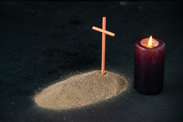 Vista frontale della piccola tomba con candela accesa sul nero