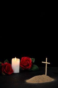 Front view of little grave with candle and red roses on black