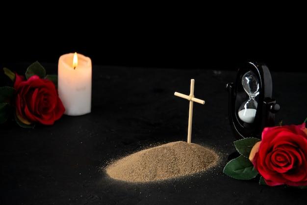 Vista frontale della piccola tomba con candela e rose rosse su fondo nero