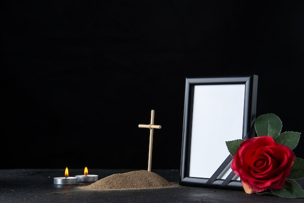 Front view of little grave with cross and picture frame on dark