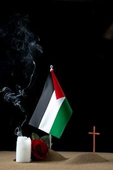Vista frontale della piccola tomba con bandiera palestinese su fondo nero