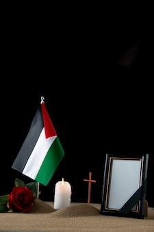 Front view of little grave with palestinian flag on black