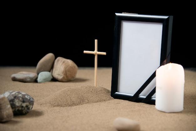 Vista frontale della piccola tomba con cornice di pietre e candela