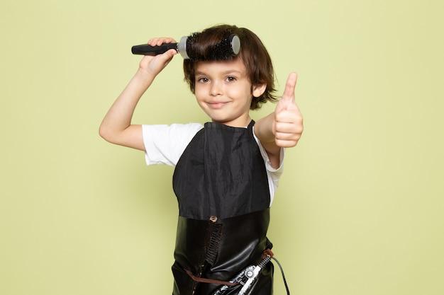 Un bambino adorabile del piccolo parrucchiere di vista frontale nella posa del mantello nero