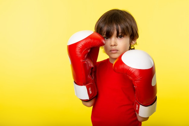 A front view little kid cute adorable in blue boxing gloves and red t-shrit on the yellow wall