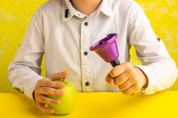 Front view little kid holding green apple and purple bell on yellow surface