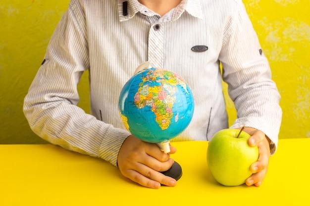 黄色い表面に小さな地球儀と青リンゴを持っている正面図小さな子供