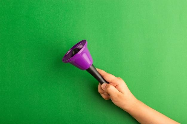 Вид спереди маленький ребенок держит фиолетовый колокольчик на зеленой поверхности