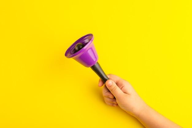 Vista frontale ragazzino che tiene campana viola sulla superficie gialla