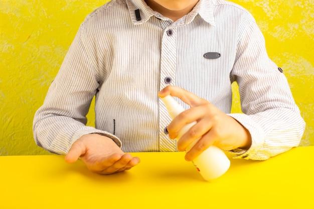 Vista frontale ragazzino utilizzando spray come misura di prevenzione sulla superficie gialla