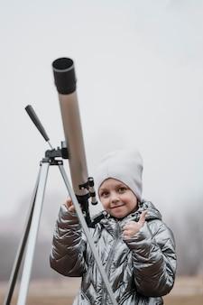 Vista frontale ragazzino utilizzando un telescopio