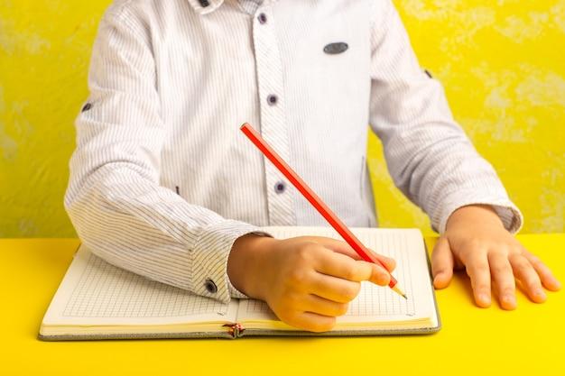 Vista frontale ragazzino che scrive e disegna sulla superficie gialla