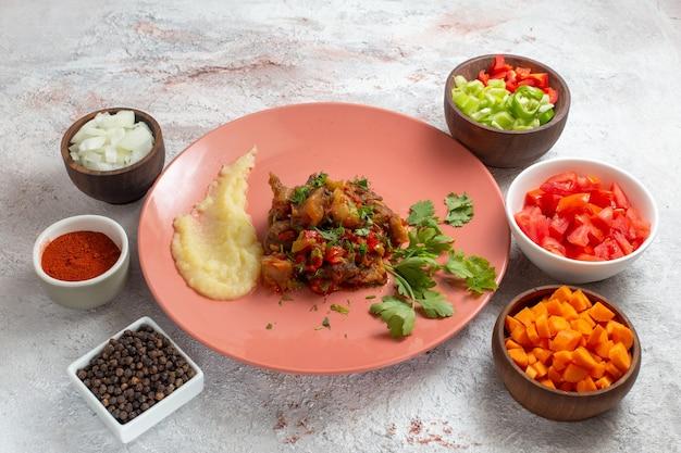 흰색 표면에 얇게 썬 고추 샐러드와 조미료와 함께 전면보기 작은 고기 조각