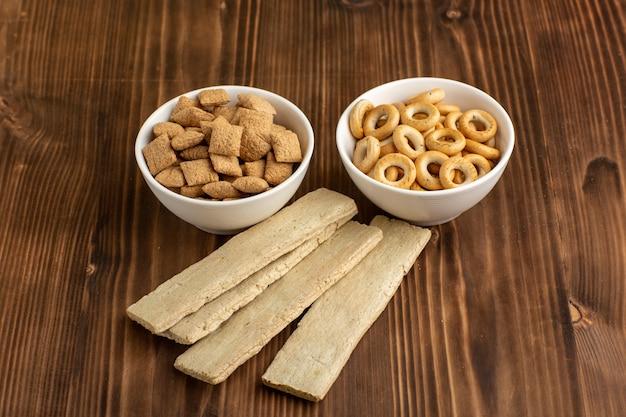 Маленькие подушки, печенье с крекерами на коричневом столе, вид спереди