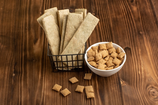 Вид спереди маленькое печенье подушечки с крекерами на коричневом деревянном столе