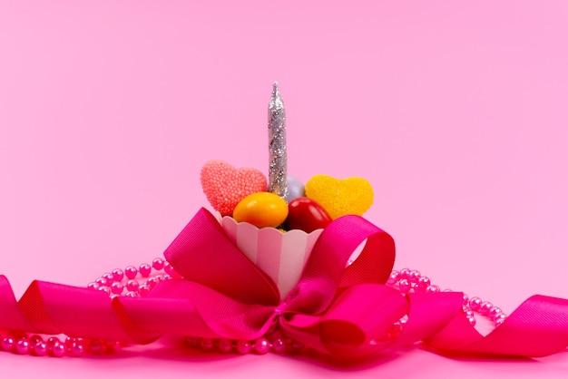 Un piccolo regalo di vista frontale con caramelle e candela d'argento progettata con rosa, fiocco isolato su rosa, presente festa di compleanno