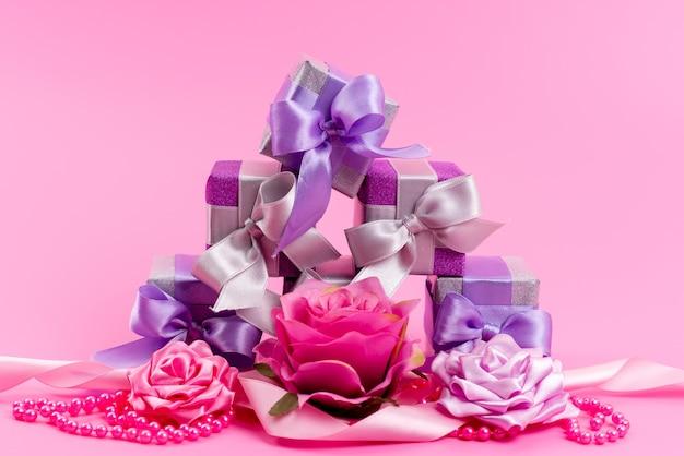 Una vista frontale piccole scatole viola con piccoli fiori disegnati sulla festa di compleanno regalo rosa e presente