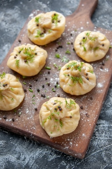 Front view little raw dumplings on a light gray surface meat cuisine meal dough cooking dish cake dinner
