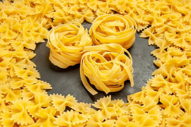 Front view little raw pasta on dark photo many dough italian pasta color food meal