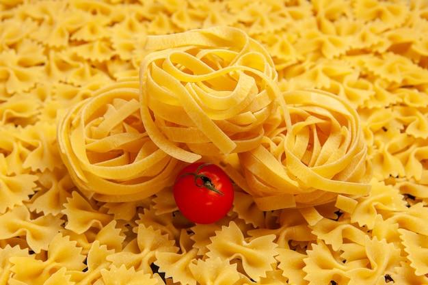 Vista frontale poca pasta cruda pasta alimentare pasto colore molte foto pasta italiana