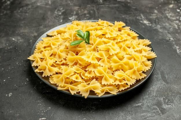 暗い灰色の写真の食事の皿の中の小さな生パスタの正面図、イタリアのパスタ生地の色多く