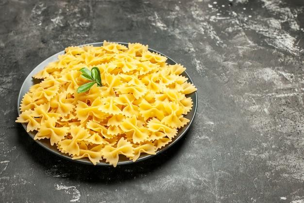 暗い灰色の写真の食事の皿の中の小さな生パスタの正面図