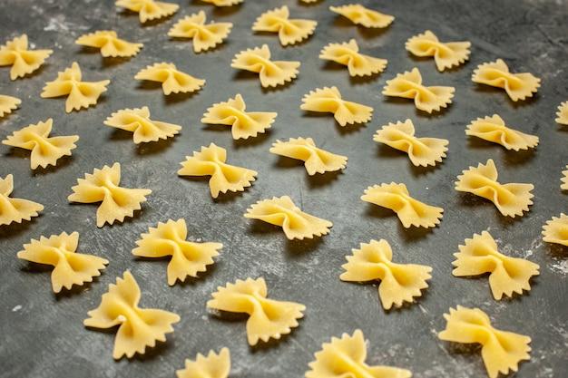 Вид спереди маленькие сырые макароны, выложенные на темно-сером много пищевого красителя, фото, тесто для еды, итальянская паста