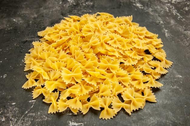 Вид спереди маленькие сырые макароны на темно-сером пищевом цвете. многие итальянские макаронные изделия из теста.