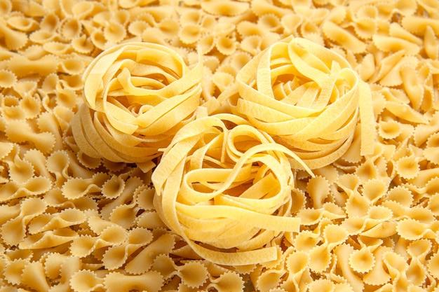 Вид спереди маленькие сырые макароны на свету много муки из теста цвет фото еда