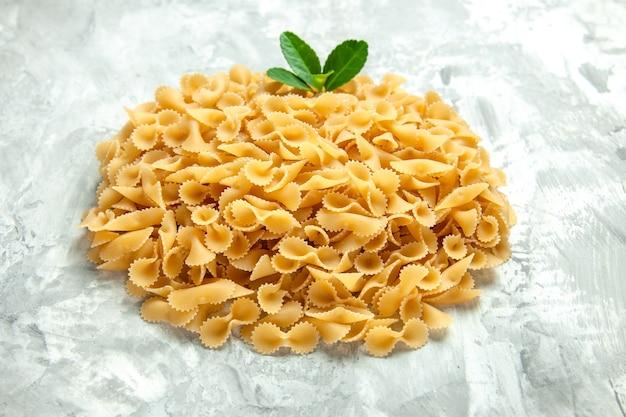 Вид спереди маленькие сырые макароны на светлом фото пищевой краситель много теста