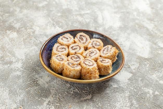 흰색 테이블 사탕 confiture 달콤한 차에 접시 안에 전면보기 작은 롤 사탕
