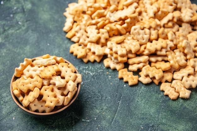 Vista frontale piccoli cracker salati all'interno del piatto e su sfondo scuro colore croccante cips sale pepe pane fette biscottate secche