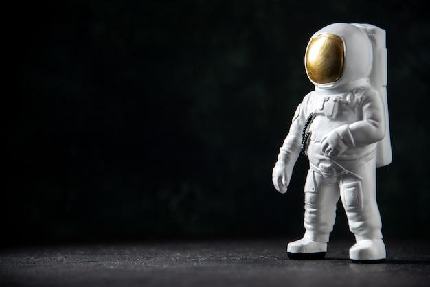 Vista frontale del piccolo giocattolo dell'astronauta sul nero