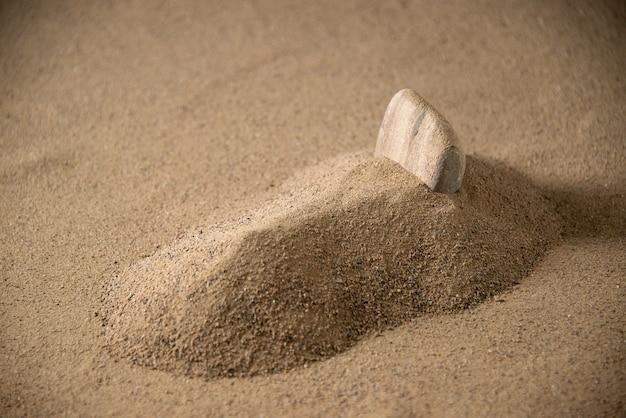 Vista frontale della piccola tomba di pietra sulla sabbia lunare