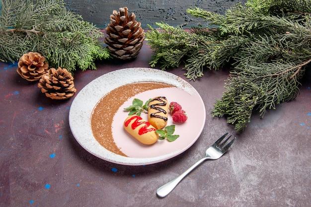 Vista frontale piccoli biscotti dolci all'interno del piatto progettato su uno spazio scuro