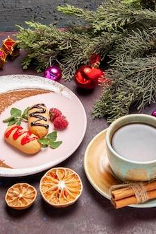 Vista frontale piccoli biscotti dolci con una tazza di tè su uno spazio buio