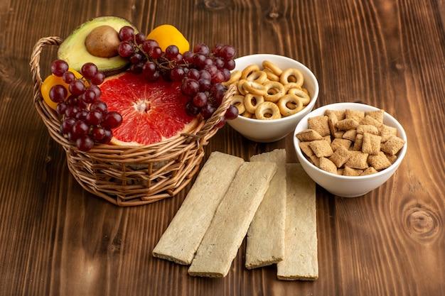 茶色の机の上にさまざまな果物と小さな甘いクッキーの正面図