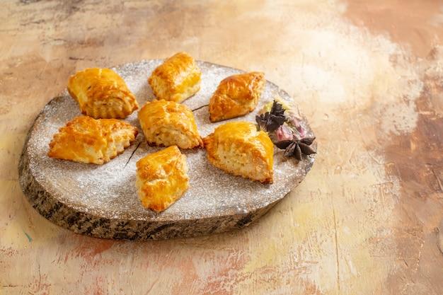 Вид спереди маленькие сладкие пирожные для чая на светлом столе, сладкий пирог, пирожное