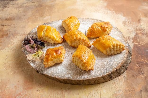 Vista frontale piccoli pasticcini dolci per il tè su una torta dolce della pasticceria della torta del tavolo leggero