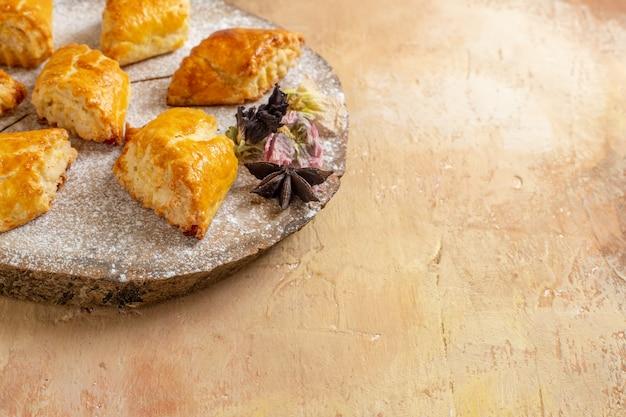 Pasticcini dolci di vista frontale piccoli per il tè sulla torta dolce della pasticceria della torta del tavolo luminoso