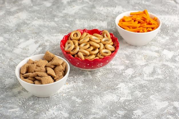 Vista frontale piccoli cuscini dolci biscotti e cracker con fette biscottate su superficie bianca
